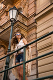 Longhaired hippy girl with sunglasses stands near old town stree Royalty Free Stock Photo