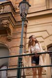 Longhaired hippy lady with sunglasses near old town streelight Stock Images