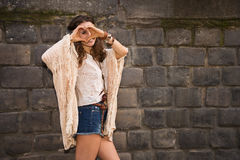 Longhaired hippy young woman near stone wall making heart hand Royalty Free Stock Images