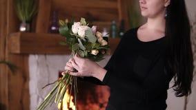 Longhaired kvinnlig blomsterhandlare som rymmer en halva gjord bukett och tillfogar blommor och växter till sammansättning Planlä stock video