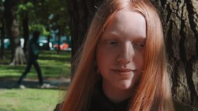 Longhaired redhead pretty girl smiling under park tree stock video footage