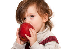 Longhaired toddler eating apple Royalty Free Stock Photos