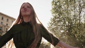 Longhaired vrij foxy meisje in het groene kleding spinnen bij stadsvierkant stock videobeelden