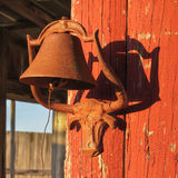 Longhorn steer bell holder. A rusty old bell held by a steer bracket screwed to a barn wall near sunset Royalty Free Stock Photos