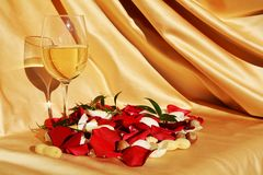 Longing for affection. Red petals of roses on an elegant golden background, next to a glass of wine, suggesting affection expectations Stock Photos