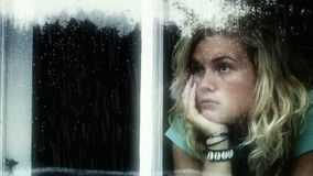 Longing girl a rainy day. Young girl looking out of a window a rainy day, looking sad stock footage