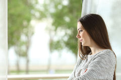Longing woman looking through window at home Stock Image