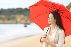 Longing woman thinking looking at horizon. Portrait of a longing woman thinking and looking at horizon under a red umbrella on the beach with the sea in the royalty free stock photos