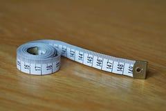 Longitud de medición de la cinta métrica en los centímetros y los metros, usados con frecuencia para medir el perímetro del cuerp Imágenes de archivo libres de regalías