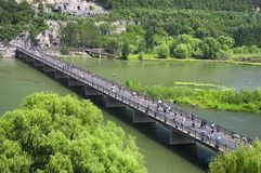 Longmen Grottoes Scenic Area Luoyang China. Chinese tourists walking over the Manshui Qiao bridge over the yi river in the longmen grottoes scenic area on a stock images