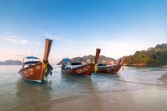 Longs bateaux thaïlandais traditionnels se tenant près du bord de la mer blanc de sable des îles de Phi Phi, Thaïlande photo libre de droits