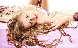 Longs cheveux bouclés de femme détendant sur son lit au matin photographie stock libre de droits