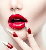 Longs clous rouges et lèvres brillantes rouges Photos libres de droits