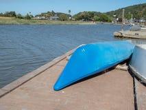 Longs kayaks dormants se reposant sur un dock donnant sur une rivière dans un voisinage ensoleillé photos libres de droits