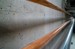 Longs nouveaux tuyaux de cuivre brillants menant le long d'un mur en béton de cave photo stock