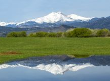 Snow Capped Longs Peak Reflecting in the waters on a spring day. Longs Peak reflects in the waters along a country road in Longmont Colorado stock photos