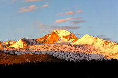 Longs Peak at sunrise. Panorama View of Longs Peak at sunrise with pink clouds forming over the summit Royalty Free Stock Photo