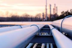Longs tuyaux en acier dans l'usine de pétrole brut pendant le coucher du soleil photo stock