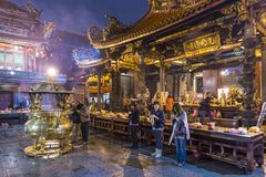 Longshan Temple in Taipei. TAIPEI, TAIWAN - JANUARY 12, 2013: Worshippers at Longshan Temple. The temple was built in 1738 by settlers from Fujian royalty free stock photos