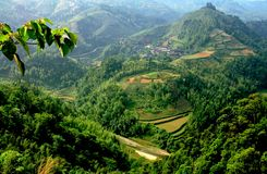 Longsheng, China: Mountainside Rice Paddies. Vista over the hilly forested mountainsides terraced rice paddies and a distant village in Longsheng in China's Stock Photos