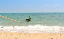 Longtail-bateau ancré sur la plage avec la corde Photo stock
