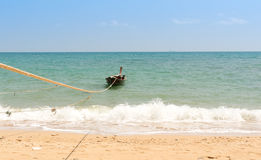 Longtail-Boat anchored on the beach with rope Stock Photo