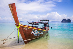 Longtail boat on beach in Thailand. Longtail boat in crystal clear blue waters waiting for passengers on beautiful white beach in Ko Mok, Thailand Stock Image