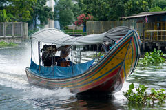Longtail boat on a canal in Bangkok, Thailand. Longtail boat at speed on a canal in Bangkok, Thailand stock image