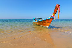 Longtail boat on clear water a beach in Thailand Stock Photo