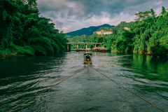 Longtail boat drag raft on green jungle river kwai in sai yok,ka Royalty Free Stock Images