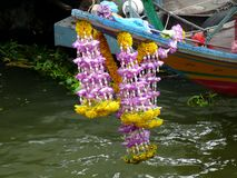 Longtail Boat`s Garland of Flowers for Good Luck. Garlands or flowers tied to the bow of the longtail boats are there to provide protection and good luck.  The stock photos