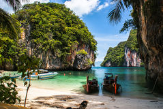 Longtail boat on the shore of a tropical island, surrounded by c. Longtail boat on the beach, surrounded by cliffs, on the island of Koh Lao La Ding. Krabi Royalty Free Stock Photography