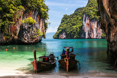 Longtail boat on the shore of a tropical island, surrounded by c. Longtail boat on the beach, surrounded by cliffs, on the island of Koh Lao La Ding. Krabi Stock Images