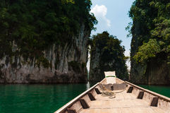 Longtail boat stopped at granite rock, Cheow Lan Lake, Thailand Royalty Free Stock Photos