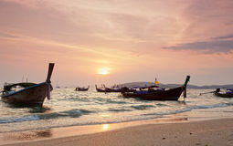 Longtail boats against a sunset. Royalty Free Stock Photography