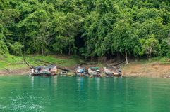 Longtail boats floating on emerald green waters. Longtail boats floating on the emerald green waters of Cheow Lan Lake inside the Khao Sok national park in Stock Images