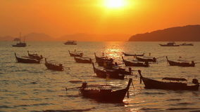 Longtail boats on seashore at sunset stock video footage