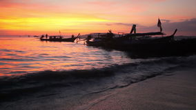 Longtail boats on seashore at sunset stock footage