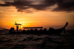 Longtail-Boot im Meer bei Sonnenuntergang in Thailand stockbild