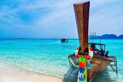 Longtail fartyg på den sandiga stranden tropiskt hav Arkivfoto