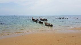 Fisherman boats on the Beach. Longtailboat on the Andaman sea in the morning at high tide connected with a rope Stock Photo