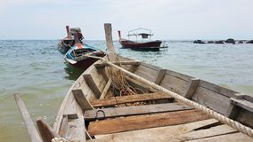 Longtailboats on Andaman Sea in the pier. PIC shows longtailboat on the Andaman sea - colours blue red brown green. Cloudy scenery for postcards or background Royalty Free Stock Photos
