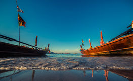 Longtale boat at the Thai beach. Paradice sand beach place. Boats on the clear water and blue sunrise sky. Royalty Free Stock Photography