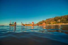 Longtale fartyg på den thailändska stranden Ställe för Paradice sandstrand Fartyg på det klara vattnet och blåttsoluppgånghimlen Royaltyfri Foto