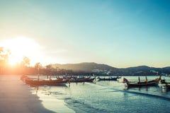 Longtale fartyg på den thailändska stranden Ställe för Paradice sandstrand Fartyg på det klara vattnet och blåttsoluppgånghimlen Arkivbild