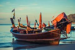 Longtale fartyg på den thailändska stranden Ställe för Paradice sandstrand Fartyg på det klara vattnet och blåttsoluppgånghimlen Royaltyfri Fotografi