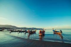 Longtale fartyg på den thailändska stranden Ställe för Paradice sandstrand Fartyg på det klara vattnet och blåttsoluppgånghimlen Royaltyfria Bilder