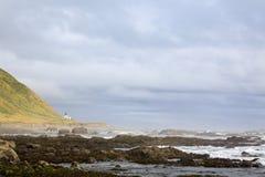 Longtemps au loin la plage rocheuse mène au phare perdu de côte sur le point Image libre de droits