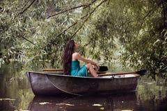 Longue brune de cheveux dans une robe se reposant sur le bateau images stock