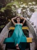Longue brune de cheveux dans une robe se trouvant sur le bateau photos stock